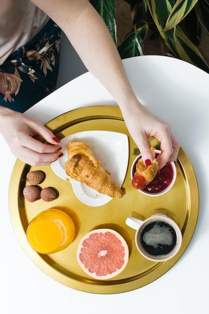 Petit déjeuner français avec croissant et café. les mains des femmes cassent un croissant. café, confiture, croissant, jus d'orange, pamplemousse, litchi. Photo Premium