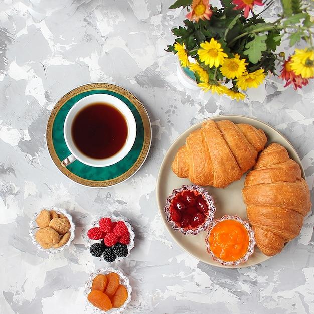 Petit déjeuner français avec croissants, confiture d'abricot, confiture de cerise et une tasse de thé, fleurs rouges et jaunes Photo gratuit