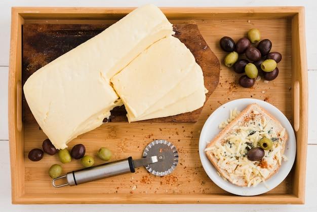 Petit déjeuner de fromage râpé aux olives sur du pain dans un plateau en bois Photo gratuit