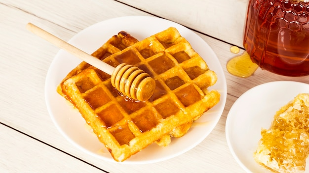 Petit déjeuner avec des gaufres belges et du miel Photo gratuit