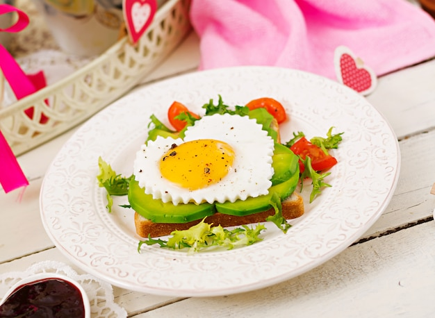 Petit Déjeuner Le Jour De La Saint-valentin - Sandwich à L'oeuf Au Plat En Forme De Cœur, Avocat Et Légumes Frais. Tasse De Café. Petit Déjeuner Anglais. Photo Premium