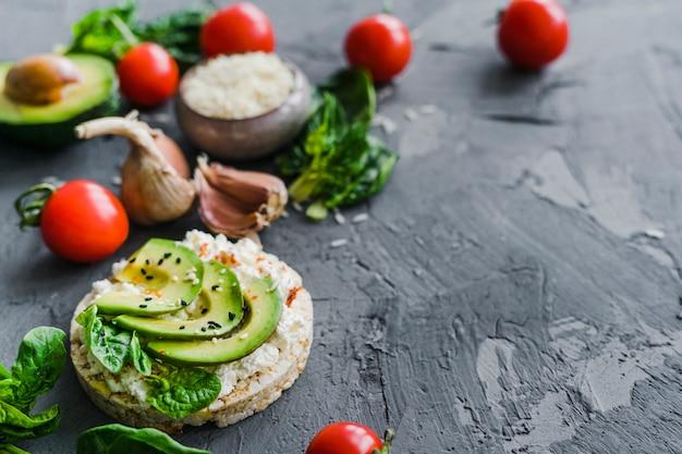 Petit-déjeuner maison avec tomates cerises; ail; avocat et riz cru sur fond Photo gratuit