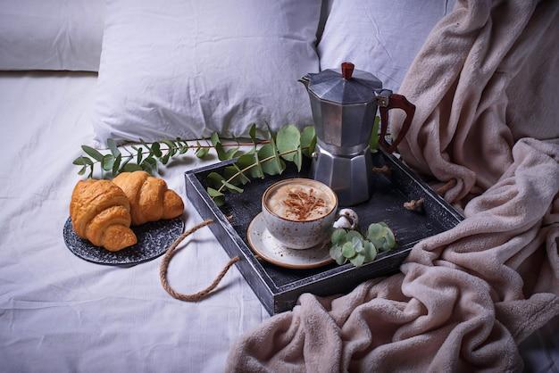 Petit déjeuner en mauvais. croissants et tasse de café Photo Premium