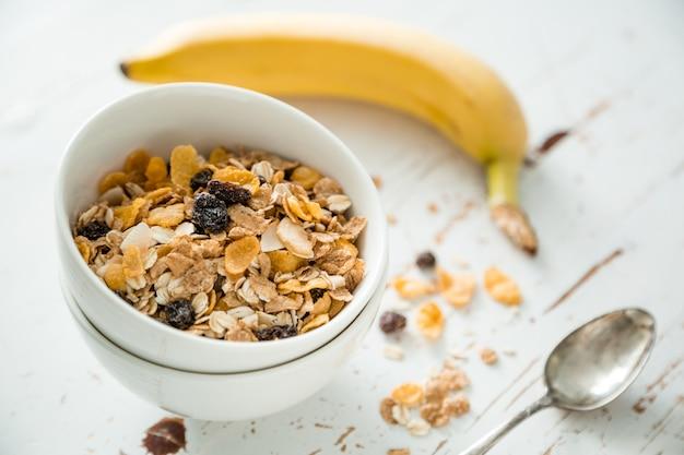 Petit déjeuner - muesli et fruits sur une table blanche Photo Premium