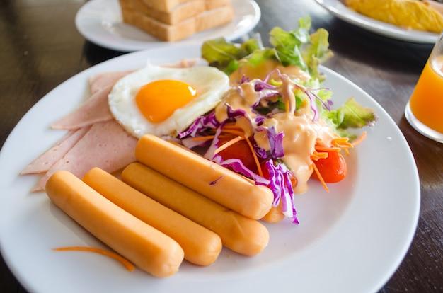 Petit déjeuner avec oeuf au plat et salade Photo Premium
