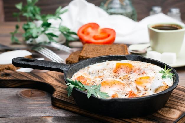 Petit déjeuner prêt à l'emploi: shakshuka à partir d'œufs au plat avec tomates et persil dans une casserole, pain au beurre et café sur une table en bois Photo Premium