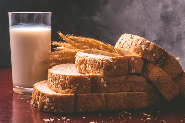 Petit déjeuner sain avec du pain de blé entier et du lait sur la table. Photo Premium