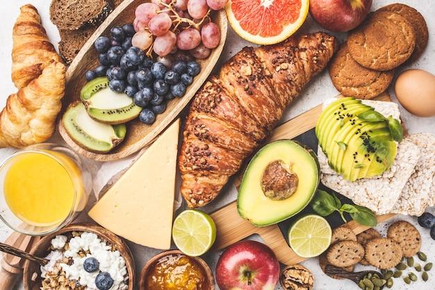 Petit-déjeuner sain et équilibré sur fond blanc. muesli, jus de fruits, croissants, fromage, biscuits et fruits, vue de dessus. Photo Premium