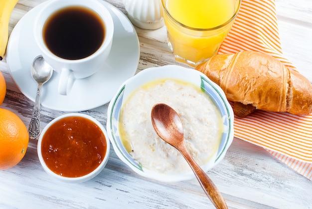 Petit-déjeuner sain avec des flocons d'avoine avec du beurre, des croissants et du café Photo Premium