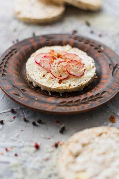 Petit-déjeuner sain avec des gâteaux de riz soufflé faits maison garnis de tranches de navet et de fromage sur une assiette Photo gratuit