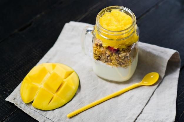 Petit déjeuner sain muesli et yaourt avec smoothie à la mangue dans des bocaux en verre. Photo Premium