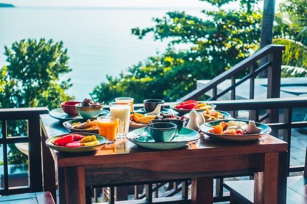 Petit-déjeuner sain avec des œufs au bacon, des crêpes au jus d'orange, du lait, du pain et du café Photo gratuit
