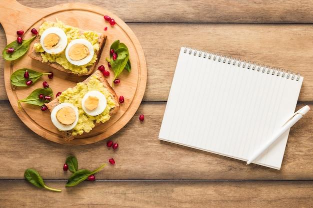 Petit-déjeuner sain sur une planche à découper avec livre de spirale vierge et stylo sur fond en bois Photo gratuit