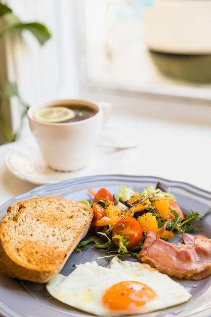 Petit déjeuner sain avec une tasse de thé sur une table blanche Photo gratuit