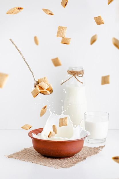 Petit-déjeuner Sec De Grains De Maïs De Céréales Avec Du Cacao Dans Un Bol D'argile Rouge Avec Du Lait Photo Premium