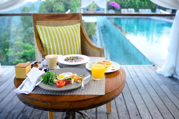 Petit déjeuner servi avec oeuf au plat, café, jus d'orange, céréales et fruits pour la santé. Photo Premium