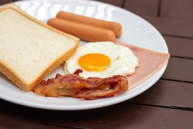 Petit déjeuner simple. pain grillé, œuf au plat, saucisse, jambon et bacon. Photo Premium