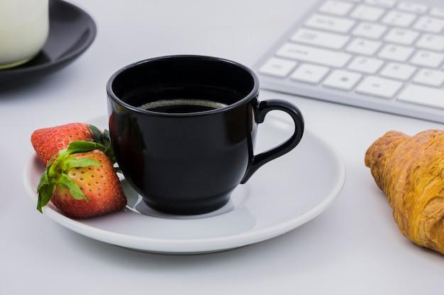 Petit déjeuner avec une tasse de café et des fruits Photo gratuit