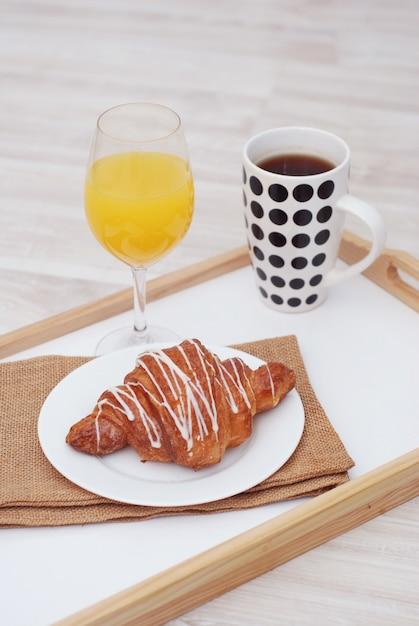 Petit déjeuner. tasse à thé, croissant et verre de jus. Photo Premium