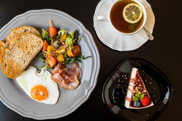 Petit déjeuner; thé au citron; gâteau au fromage aux baies o fond noir Photo gratuit