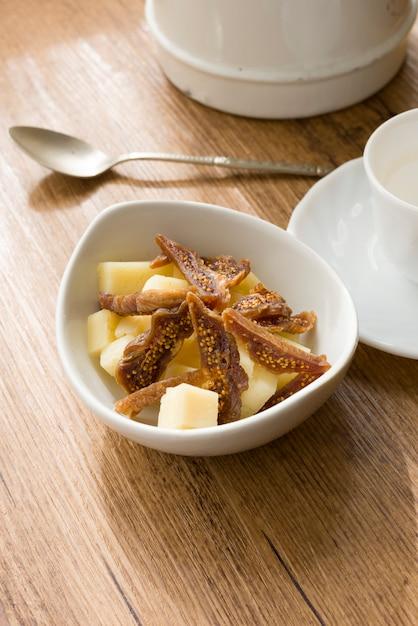 Petit-déjeuner de tranches de figue séchée avec pecorino à côté d'une tasse de café Photo Premium