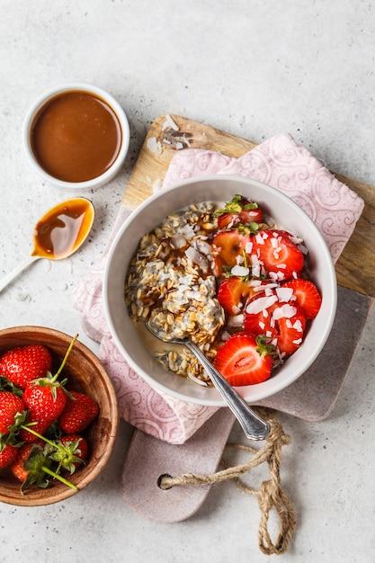 Petit déjeuner végétalien. gruau aux graines de chia, baies, graines et caramel dans un bol blanc. Photo Premium