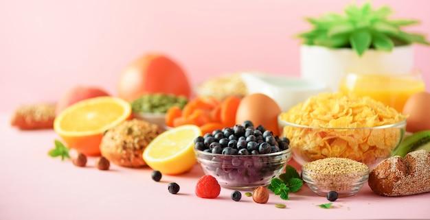 Petit déjeuner végétarien. œuf à la coque, flocons d'avoine, noix, fruits, baies, lait, yaourt, orange, banane, pêche sur fond rose. régime alimentaire sain. espace de copie. bannière Photo Premium