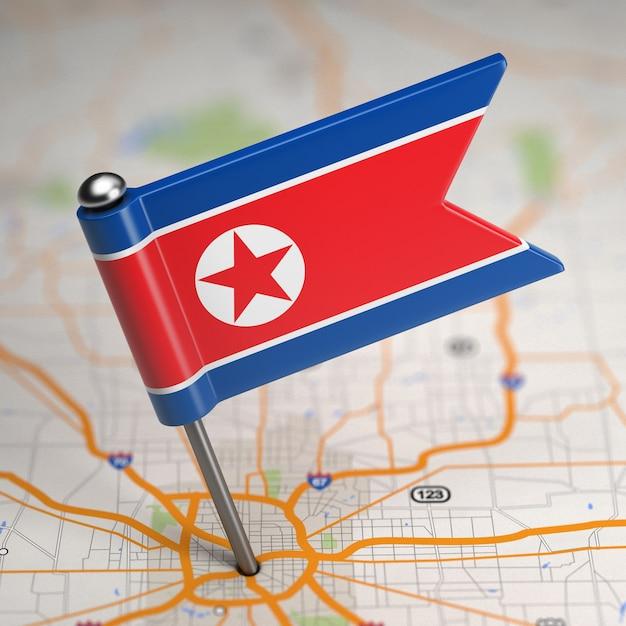 Petit Drapeau De La République Populaire Démocratique De Corée Sur Un Fond De Carte Avec Mise Au Point Sélective. Photo Premium