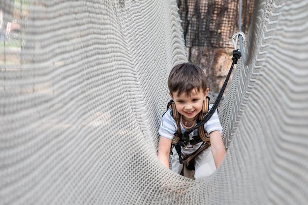 Petit enfant actif jouant sur un filet d'escalade. les enfants jouent et grimpent à l'extérieur par une journée d'été ensoleillée. Photo Premium