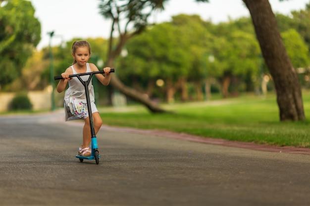Petit enfant, apprendre à conduire un scooter dans un parc de la ville sur une journée d'été ensoleillée Photo Premium