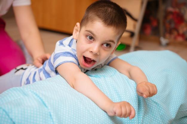 Un petit enfant atteint de paralysie cérébrale suit un traitement musculo-squelettique en faisant des exercices Photo Premium