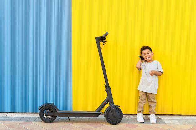 Petit enfant ayant un appel téléphonique à côté d'un scooter. Photo Premium