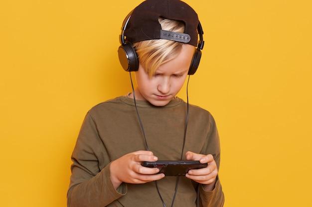 Petit Enfant Blond Garçon Enfant Jouant à Des Jeux Mobiles Sur Smartphone Et Utilisant Internet Sans Fil Tout En écoutant De La Musique Via Un Casque Photo gratuit
