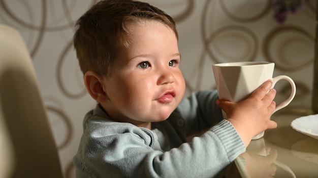 Petit Enfant Boit De L'eau Dans Une Tasse Seul. Bébé Indépendant Photo Premium