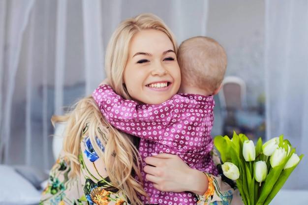 Un petit enfant embrasse maman et donne des fleurs. le concept d'enfance, d'éducation, de famille Photo Premium