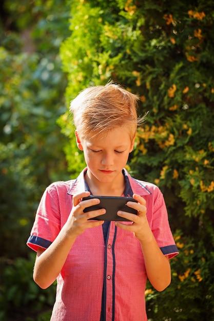 Petit enfant enfant garçon jouant à des jeux sur smartphone Photo Premium