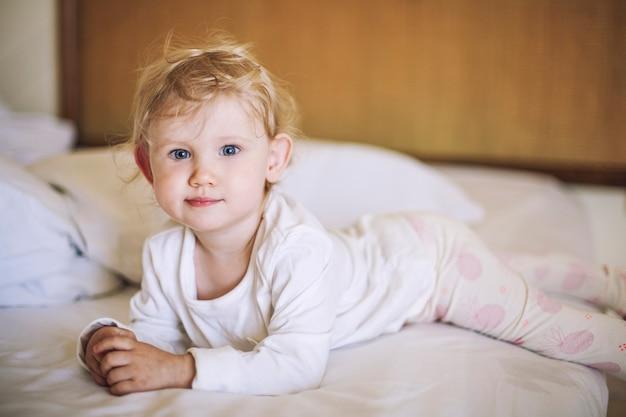 Petit Enfant Est Allongé Dans La Chambre Sur Le Lit Et Souriant Dans Mon Pyjama Photo Premium