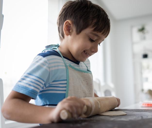 Petit Enfant Fait De La Pâte Pour Un Délicieux Bonbon Photo Premium