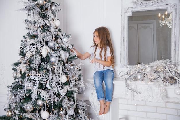 Petit Enfant Fille Décorer Un Arbre De Noël En Intérieur Classique Blanc, Assis Sur Une Cheminée Avec Miroir. Joyeux Noël, Bonne Année, Joyeuses Fêtes. Photo Premium