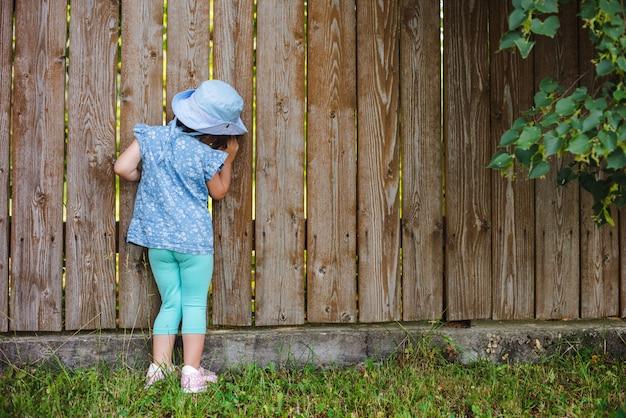 Le petit enfant en manque scintille du trou dans la clôture dans le monde en dehors de sa cour. Photo Premium