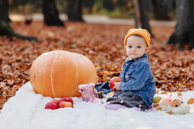 Petit enfant mignon dans le parc sur une feuille jaune avec citrouille en automne Photo Premium