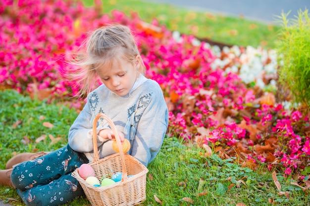 Petit enfant portant des oreilles de lapin avec un panier rempli d'oeufs de pâques le jour du printemps en plein air Photo Premium