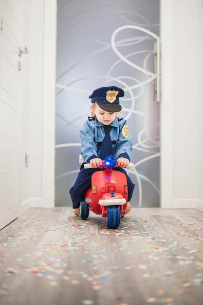 Petit enfant sur un scooter rouge habillé en policier Photo Premium