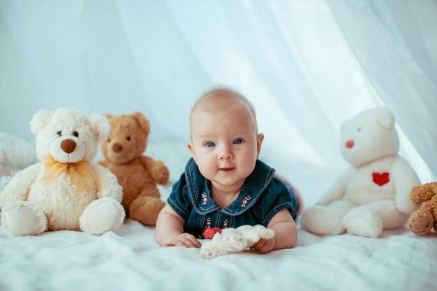 Petit enfant se trouve entre les ours jouets sur le lit Photo gratuit