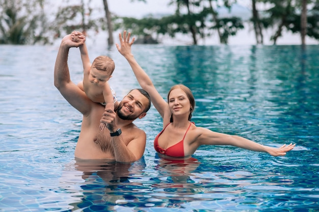 Un petit enfant et ses parents s'amusent dans la piscine pendant les vacances d'été Photo Premium
