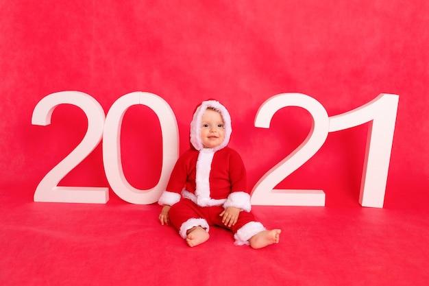 Un Petit Enfant De Six Mois Dans Un Costume De Père Noël Est Assis Près Des Grands Nombres Blancs 2021 Sur Un Photophone Isolé Rouge, Espace Pour Le Texte Photo Premium