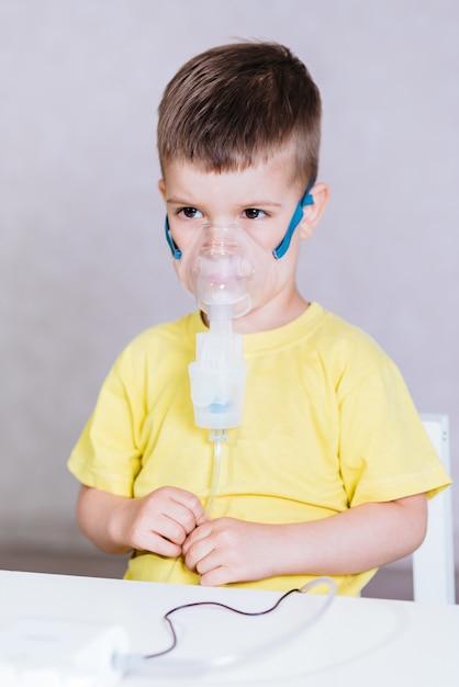 Petit enfant traite l'inhalateur de bronchite à la maison Photo Premium
