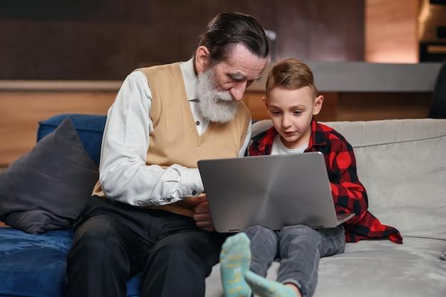 Petit-fils Apprend à Son Grand-père à Utiliser Un Ordinateur Portable. Photo Premium