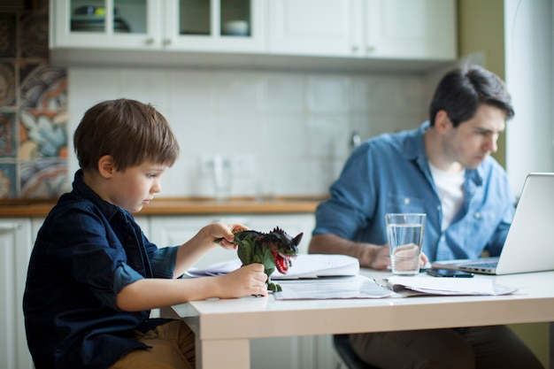 Petit fils perturbant père pigiste travaillant Photo Premium