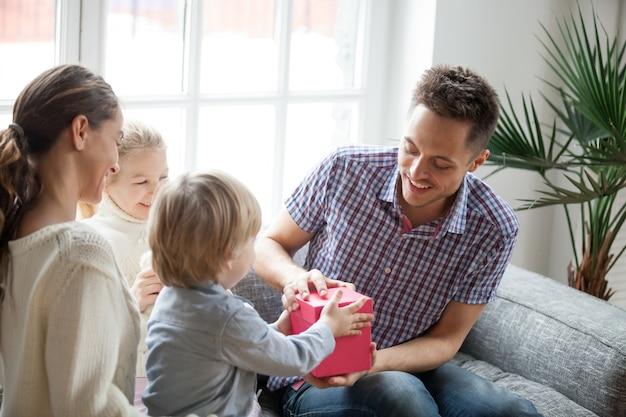 Petit fils présentant un cadeau pour papa et sa famille, fête des pères Photo gratuit